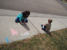The sidewalk is a bigger art canvas than anything they have inside, and using chalk is always fun.