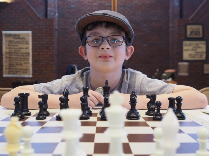 All the kids in chess club played simultaneous games against their coach. N brought along his lucky coin, but it wasn't enough to bring him victory!