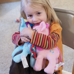 For her half-birthday, she picked out some pony stuffed animals from the toy store. As you can see, she really loves them!