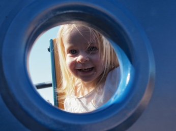 She loves looking through portholes on playground structures. This time we were at a playground that we'd never visited before, and you can tell from the expression on her face that she loved it!