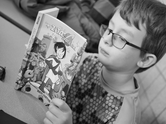 He's been enjoying graphic novels a lot lately. This is what he was doing between chess games at today's tournament.